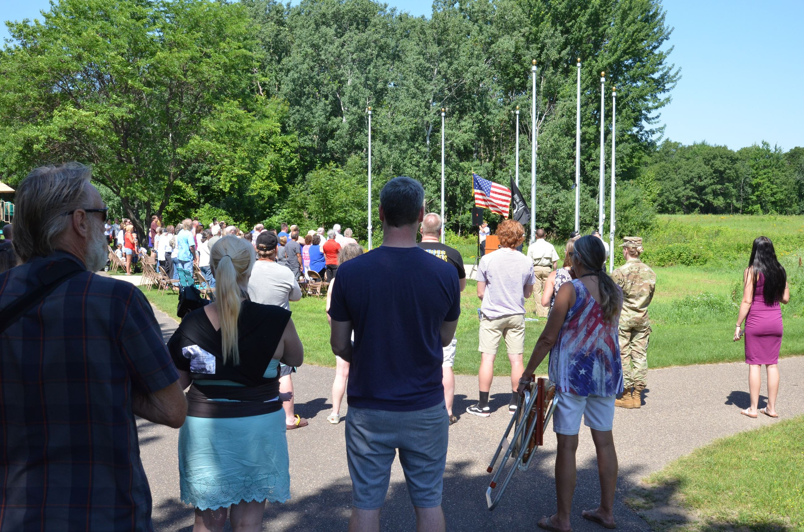 Attendees of the service stand for the flag raising